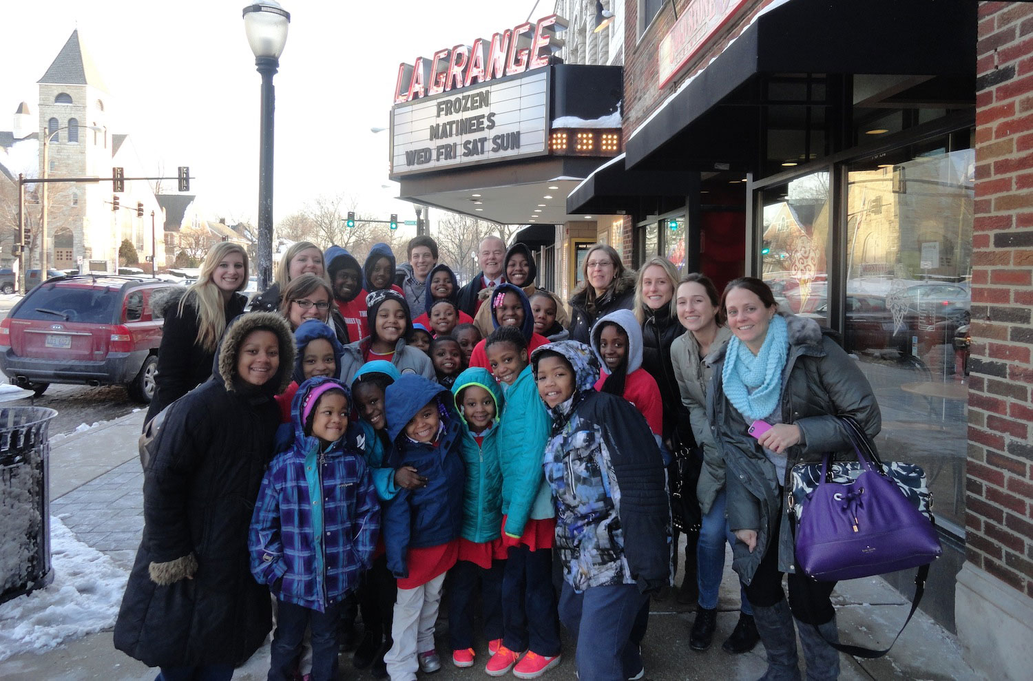 Photo of SPM employees and children of the Off The Street Club in front of the La Grange theatre.